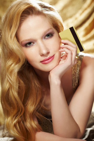 Portrait of young woman holding gold credit card