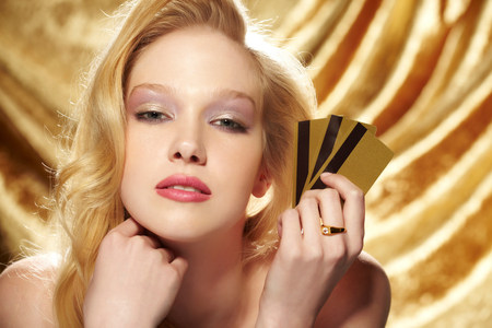 Portrait of young woman holding gold credit cards LANG_EVOIMAGES