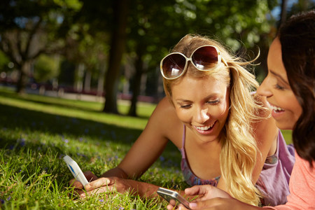 strapped: Women sharing text messages on phone