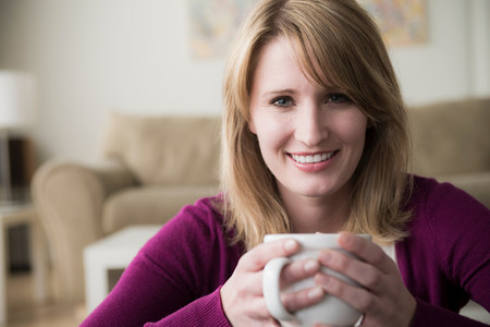refreshed: Young woman holding coffee