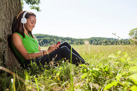 electronic music: Young woman wearing headphones sitting by tree