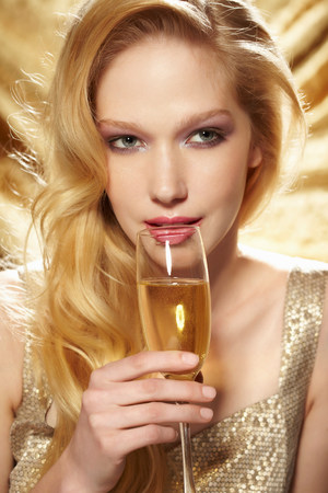 Close up portrait of young woman holding champagne flute