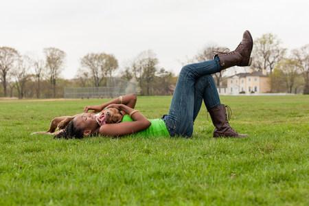 pantalones abajo: Mujer joven y su perro jugando en la hierba