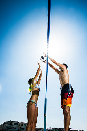 impulsive: Two beach volleyball players blocking at net LANG_EVOIMAGES