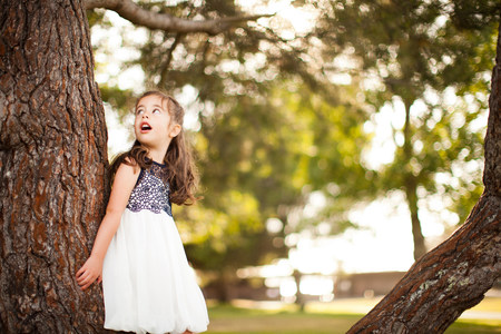 Portrait of girl leaning on tree trunk looking up