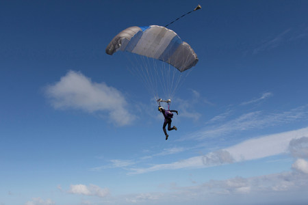 Male skydiver steering parachute