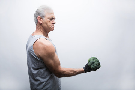 frowns: Senior man in sports clothing lifting broccoli