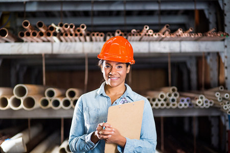 Portrait of woman in warehouse with clipboard LANG_EVOIMAGES