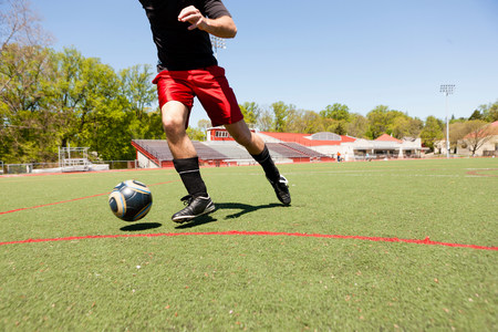 Soccer player running down pitch with ball LANG_EVOIMAGES