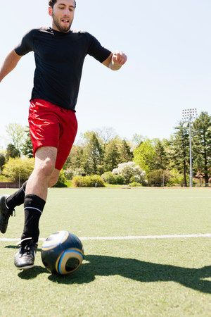Soccer player running and dribbling ball LANG_EVOIMAGES