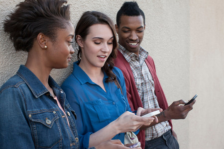 afro caribbean ethnicity: Three friends using cell phones