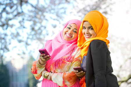 Portrait of two young woman in park with mobile phones