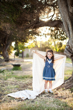 one sheet: Portrait of girl holding sheet with arms out under tree LANG_EVOIMAGES