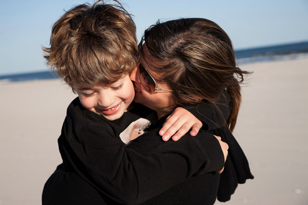 cropped out: Mother kissing son on cheek LANG_EVOIMAGES