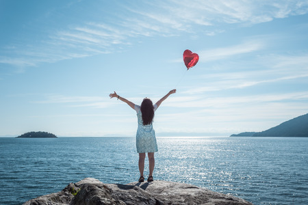 Mature woman arms outstretched with heart shaped balloon LANG_EVOIMAGES
