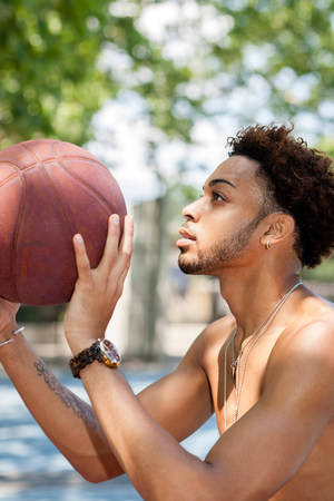 half naked: Young man holding a basketball,ready to shoot LANG_EVOIMAGES