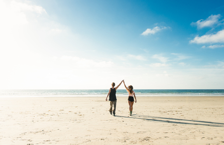 Young couple walking on San Diego beach,holding hands with arms raised