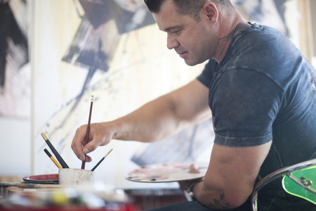new age: Mature male artist working on canvas in studio LANG_EVOIMAGES