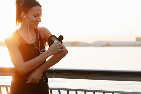 entertaining area: Young female jogger on riverside adjusting MP3 player