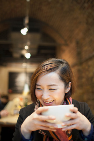 Young woman drinking coffee in restaurant LANG_EVOIMAGES