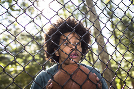 Portrait of young man holding basketball through wire fence