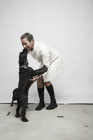 Studio shot of mature woman having fun with pet dogs LANG_EVOIMAGES
