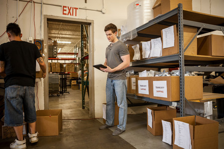 two persons only: Workers in warehouse looking at paperwork