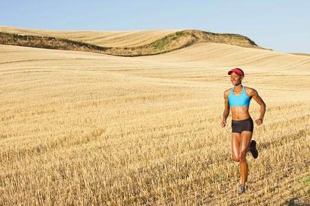 energy work: Young woman running across field,Bainbridge Island,Washington State,USA