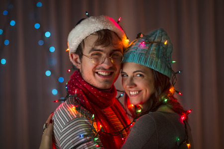 housing lot: Young couple wrapped in decorative lights at christmas