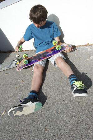 Teenage boy sitting on ground preparing skateboard