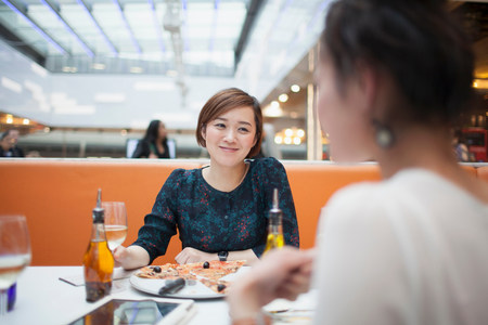 socializando: Mujeres jóvenes comiendo pizza en el restaurante LANG_EVOIMAGES