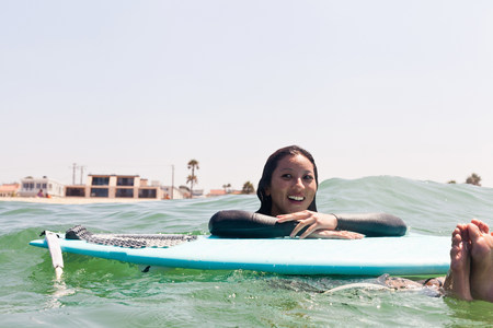 Woman floating with surfboard,Hermosa Beach,California,USA