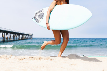 Woman running with surfboard,Hermosa Beach,California,USA LANG_EVOIMAGES