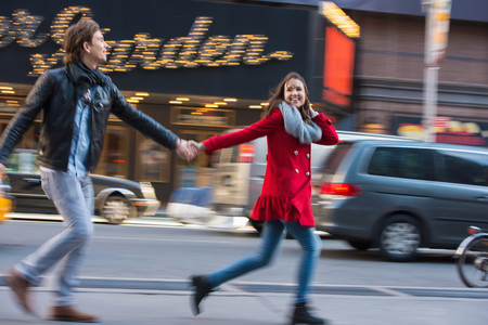 Young couple running along street, New York City, USA