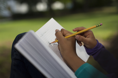 Close up of sisters in park writing in notebook