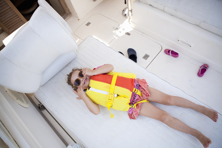 hands free device: Female toddler hiding in boat wearing lifejacket and sunglasses LANG_EVOIMAGES