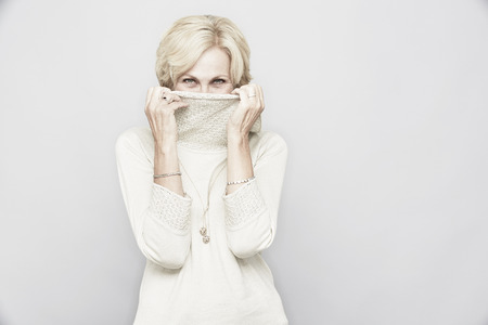 peep: Studio portrait of senior woman hiding behind roll neck LANG_EVOIMAGES