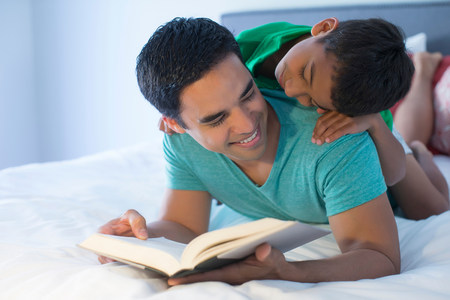 cropped out: Father and son reading on bed