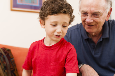 curiousness: Young boy and grandfather in sitting room