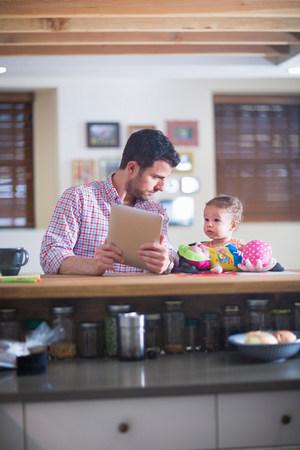 relaciones laborales: Hombre y bebé sentado en el mostrador de la cocina mirando tableta digital