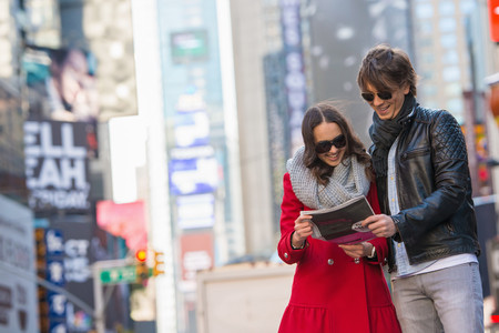 Young tourist couple looking at newspaper, New York City, USA LANG_EVOIMAGES