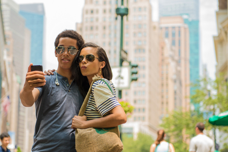 puckered lips: Couple taking photograph with mobile phone