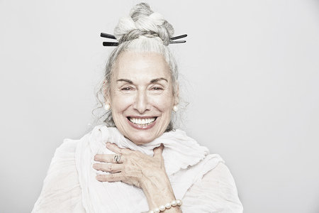 aging american: Studio portrait of sophisticated senior woman laughing