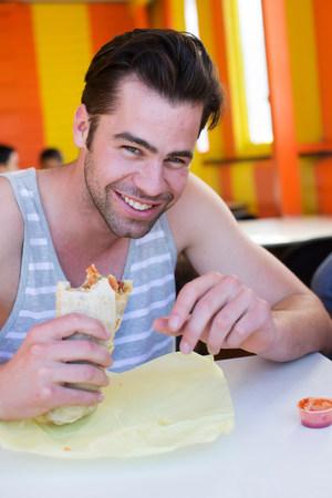 grays: Man enjoying Lebanese bread wrap