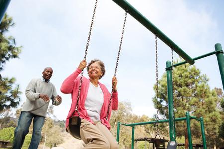 Senior man pushing woman on swing in park