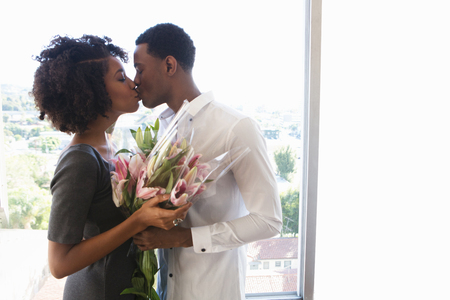 afro caribbean ethnicity: Young couple kissing,woman holding bouquet LANG_EVOIMAGES