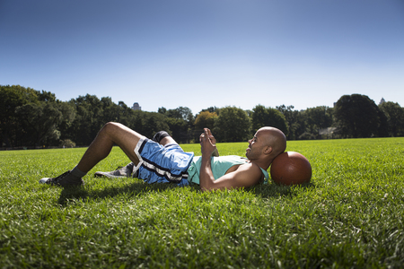Young man lying on grass with head on basketball