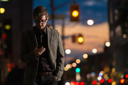 down lights: Young man strolling down street looking at mobile phone, Toronto, Ontario, Canada LANG_EVOIMAGES