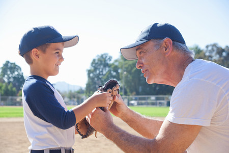 Boy and grandfather holding baseball mitt