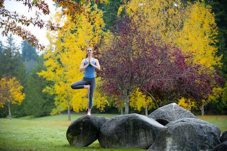 Young woman practising yoga on rock